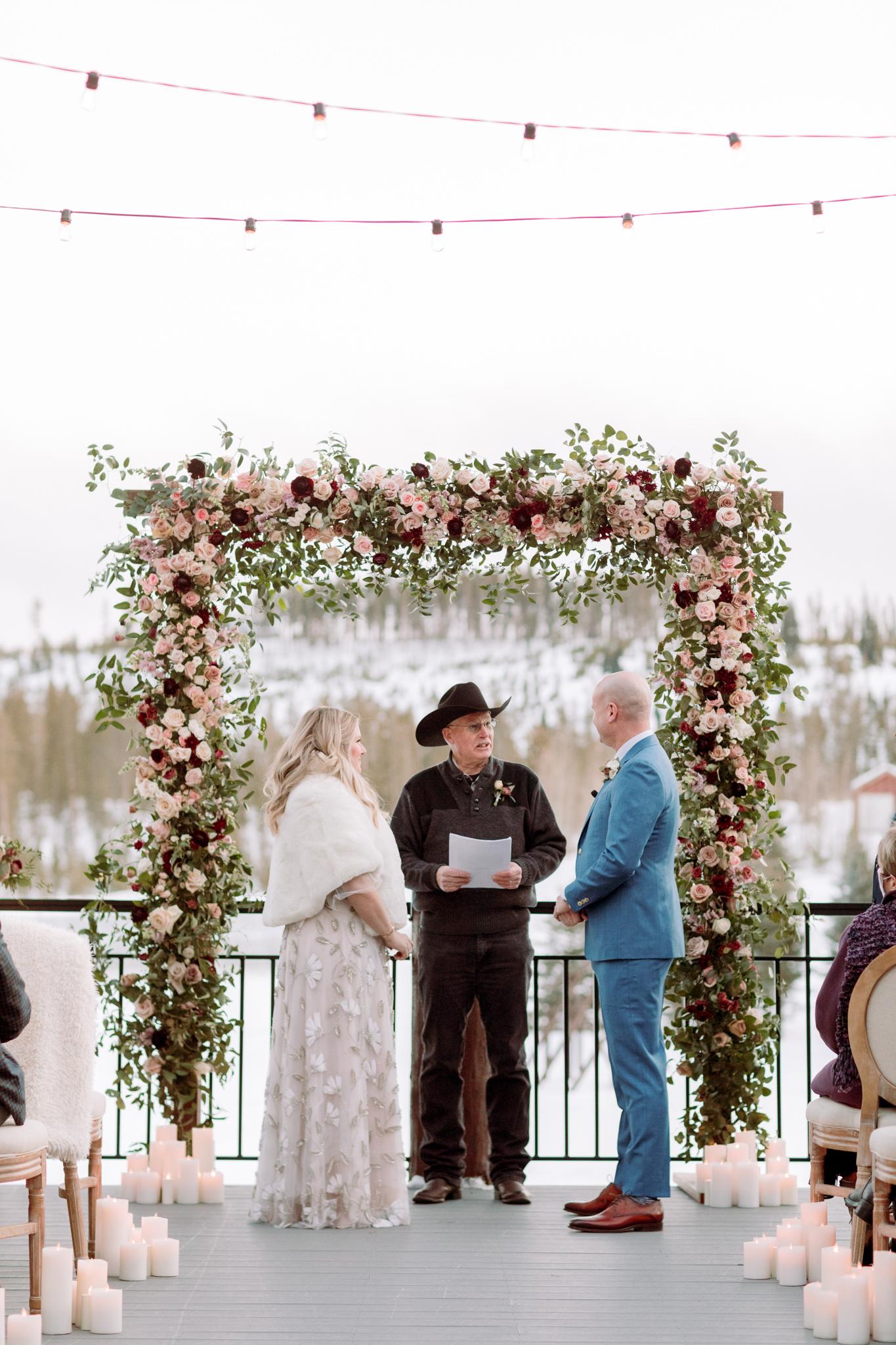 Devils-Thumb-Ranch-Tabernash-Colorado-Winter-Broad-Axe-Barn-Wedding-Deck-Ceremony-Bride-and-Groom