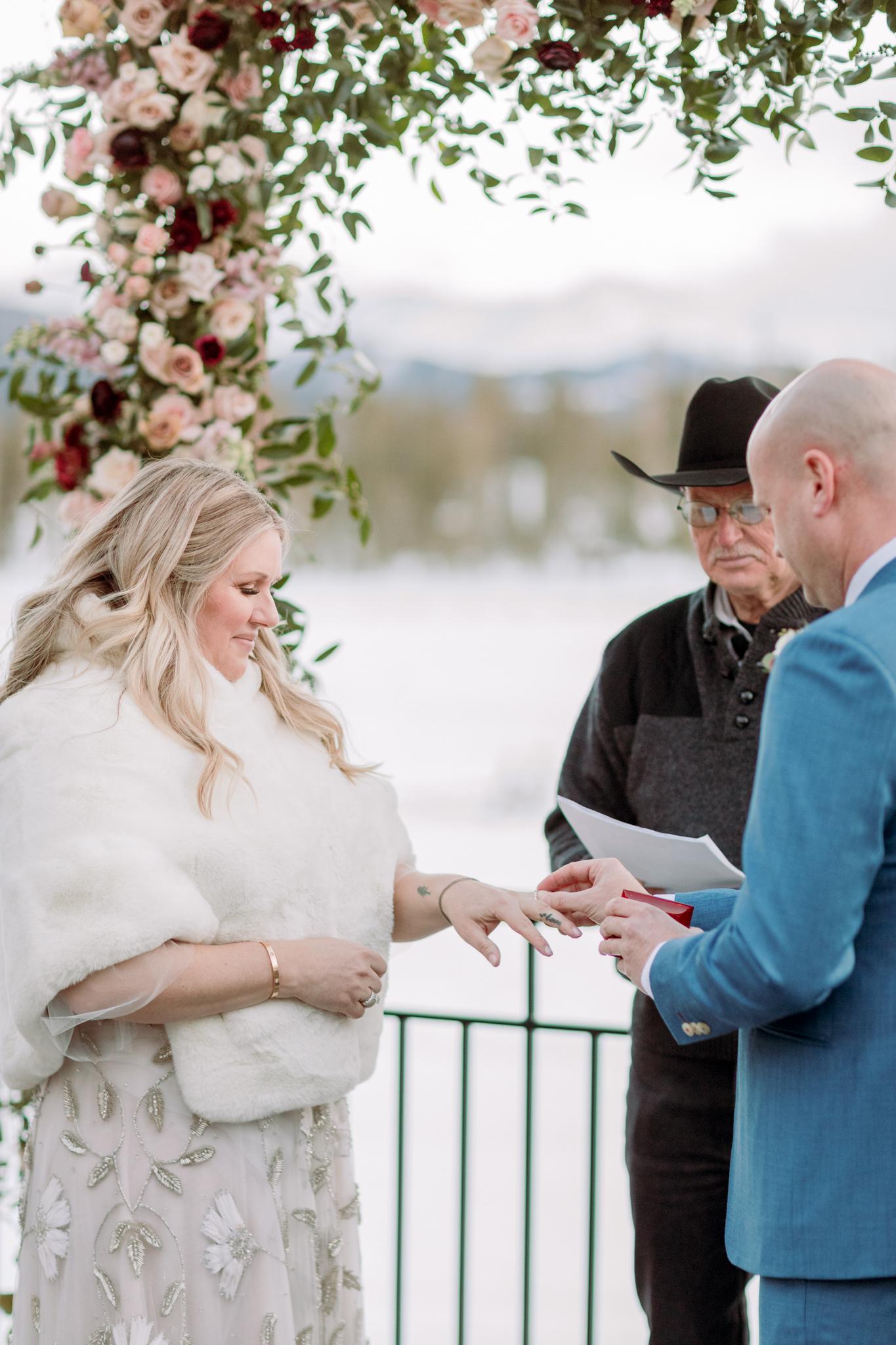 Devils-Thumb-Ranch-Tabernash-Colorado-Winter-Broad-Axe-Barn-Wedding-Deck-Ceremony-Bride-and-Groom-Rings