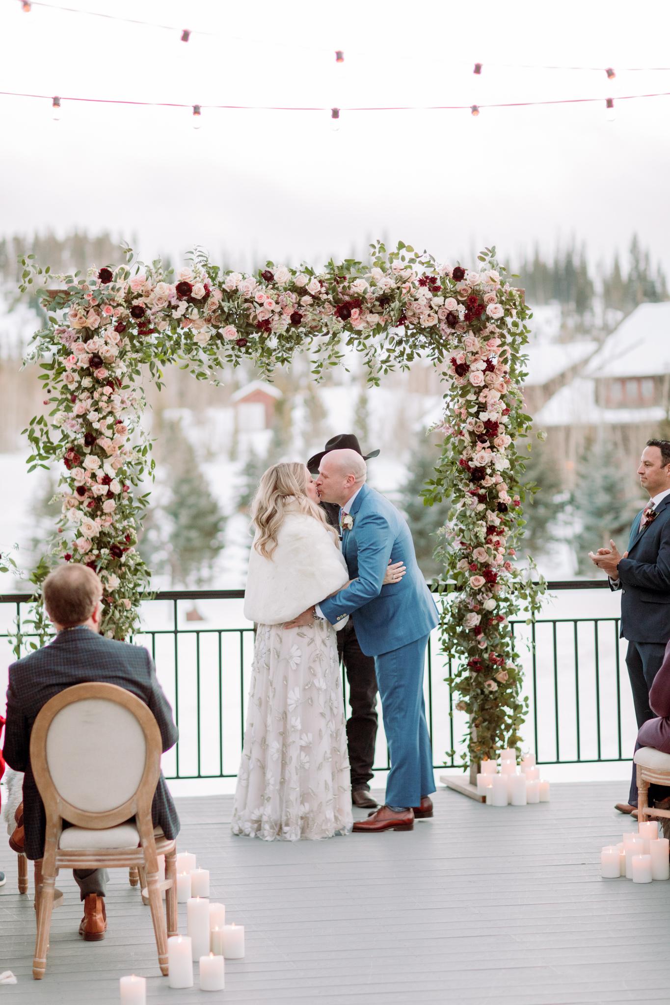 Devils-Thumb-Ranch-Tabernash-Colorado-Winter-Broad-Axe-Barn-Wedding-Deck-Ceremony-Bride-and-Groom-Kiss