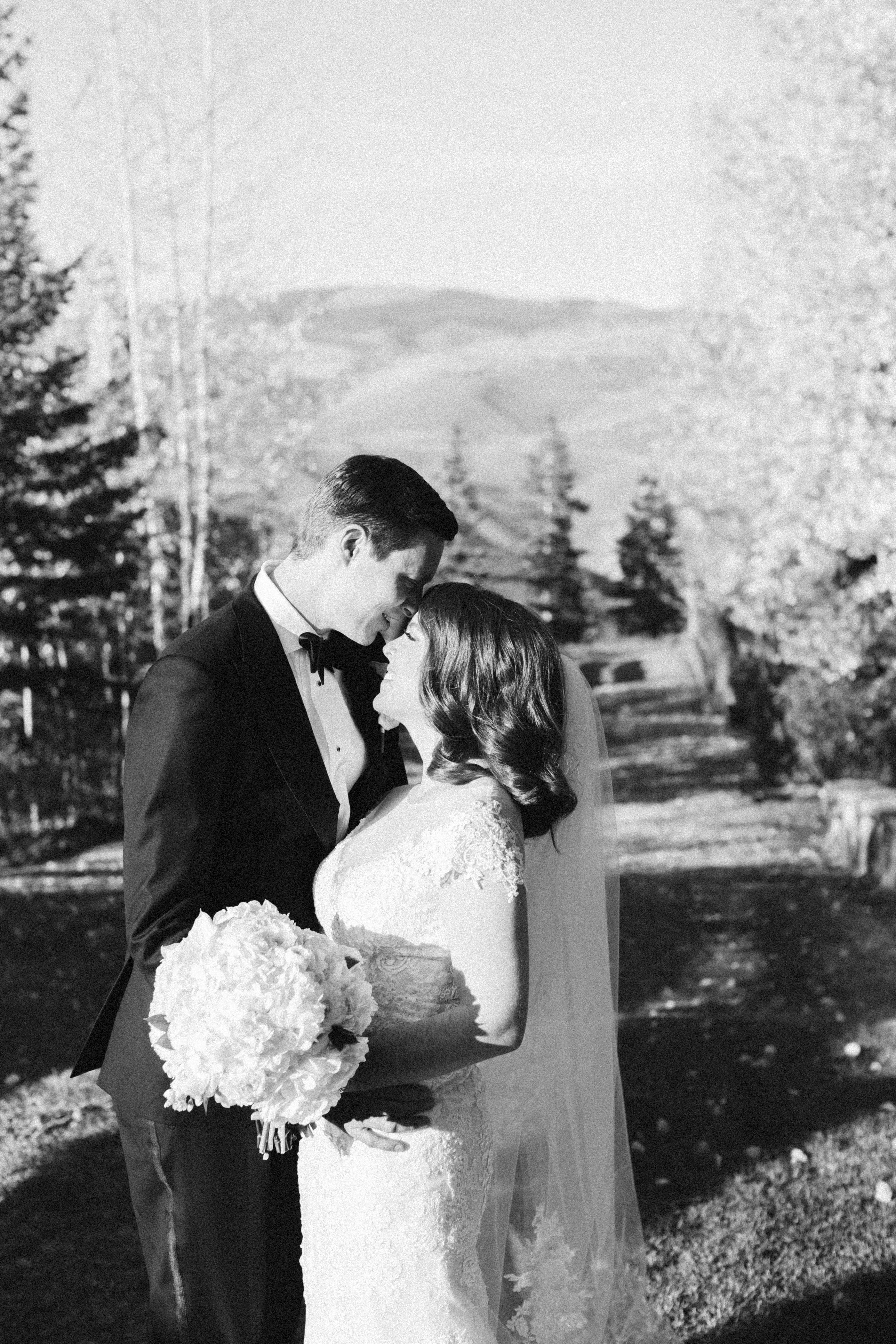 Ritz-Carlton-Bachelor-Gulch-Beaver-Creek-Colorado-Fall-Wedding-Bride-Groom-Skiers-Bridge-Black-and-White